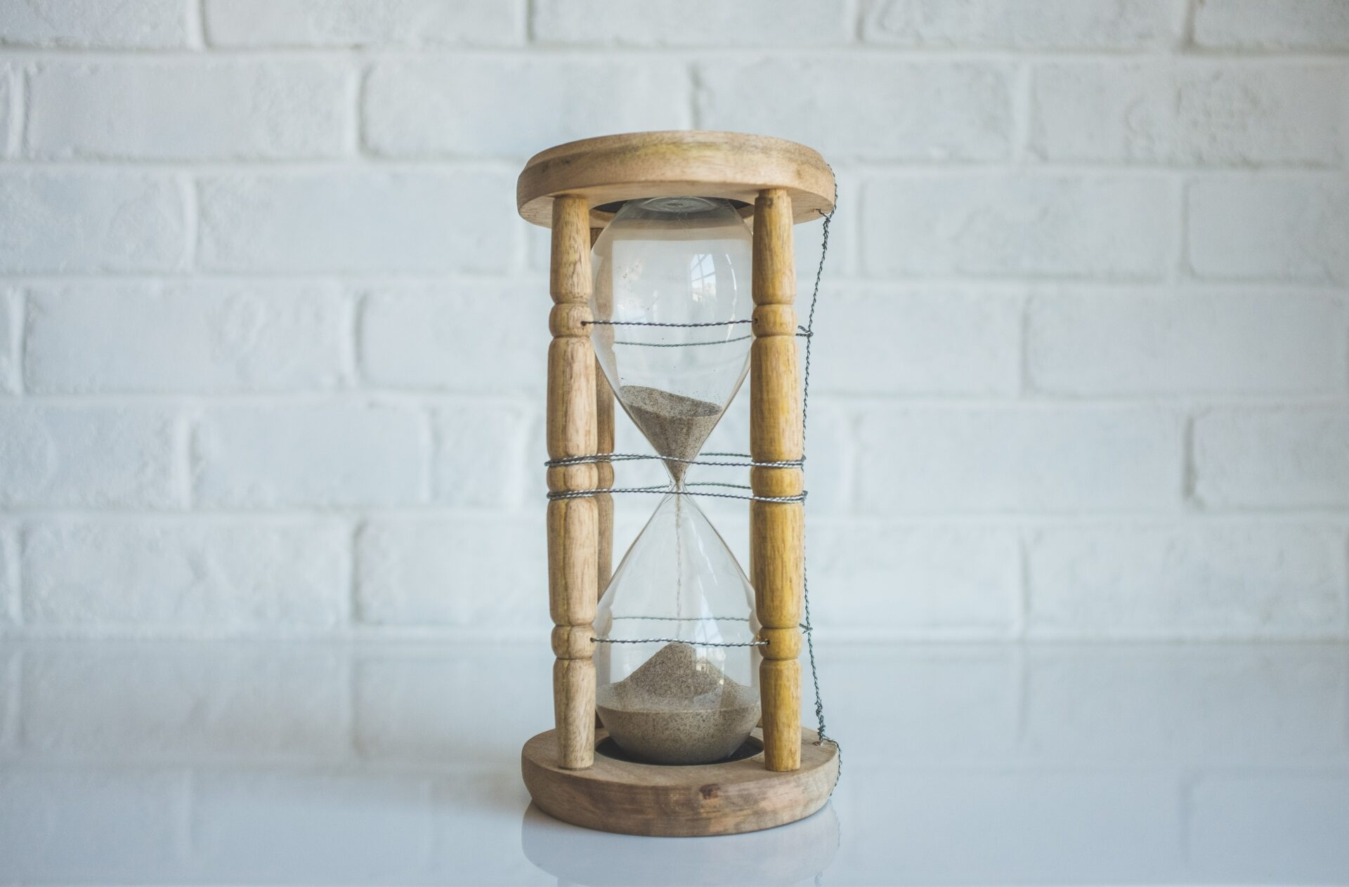 a wooden hourglass on a white tabletop in front of a white brick wall.